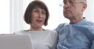 Bejaard paar die laptop thuis met behulp van stock video