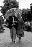 Bejaard paar die onder een paraplu in de regen lopen Zwarte en Royalty-vrije Stock Foto's