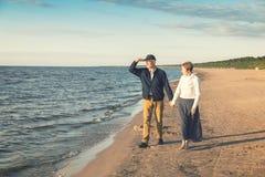 bejaard paar die romantische gang op het strand hebben stock fotografie