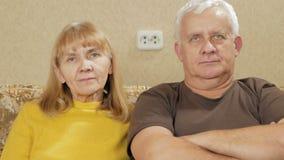 Bejaard paar die thuis op de laag rusten en de camera bekijken stock videobeelden