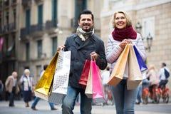 Bejaard paar lopende en dragende het winkelen zakken Royalty-vrije Stock Foto