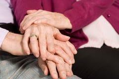 Bejaard paar met handen samen stock afbeeldingen