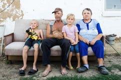 Bejaard paar met hun kleinkinderen in de werf van een dorpshuis royalty-vrije stock fotografie