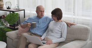 Bejaard paar met laptop en kop van koffie op bank stock videobeelden