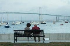 Bejaard Paar op Bank het Letten op Havenboten Stock Foto's