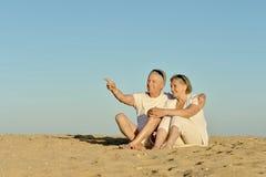 Bejaard paar op een strand Stock Foto's