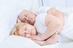 Bejaard paar in slaap in bed stock afbeeldingen