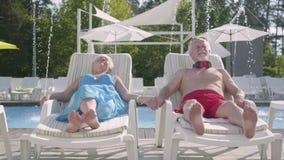 Bejaard positief paar die op sunbeds dichtbij de poolholding handen en het glimlachen liggen Gelukkige houdende van familie Rust  stock video