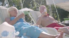 Bejaard positief paar die op sunbeds dichtbij het pool het drinken sap liggen, het spreken en het glimlachen Gelukkige houdende v stock footage