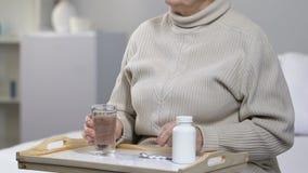Bejaard vrouwelijk geduldig nemend pil en drinkwater in het ziekenhuisruimte, gezondheidszorg voor bejaarden stock videobeelden