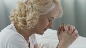Bejaard wijfje die devotedly bij haar bed bidden, die om hulp, ernstige ziekte vragen stock video