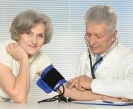 Bejaarde arts die bloeddruk meten Royalty-vrije Stock Foto's