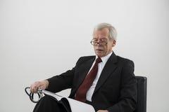 Bejaarde arts die een medisch dagboek leest Stock Afbeelding