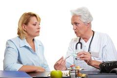 Bejaarde arts die medicijn aanbiedt Stock Foto's