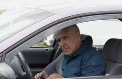 Bejaarde in auto met telefoon Royalty-vrije Stock Foto's