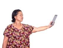 Bejaarde Aziatische vrouw die digitale tablet en rek aanbieden forw stock foto