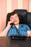 Bejaarde bedrijfsvrouw die bij telefoon spreekt Stock Fotografie