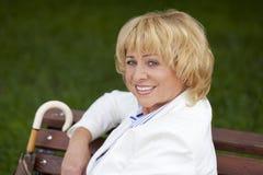 Bejaarde bedrijfsvrouw in jasjesittin op bank met dagelijks logboek Royalty-vrije Stock Afbeeldingen