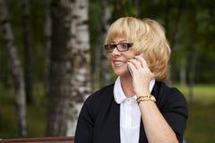 Bejaarde bedrijfsvrouw in jasjesittin op bank met dagelijks logboek Stock Fotografie