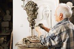 Bejaarde beeldhouwer die beeldhouwwerk maakt royalty-vrije stock afbeeldingen