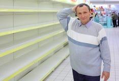 Bejaarde bij lege planken in winkelkrassen Stock Fotografie