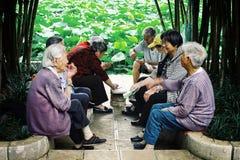 Bejaarde Chinese man en vrouwenspeelkaarten en het babbelen in een park naast een kleine vijver royalty-vrije stock foto's