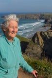 Bejaarde dame in de haar jaren '80 met wandelstok door mooie kustscène met wind die door haar haar blazen Stock Fotografie