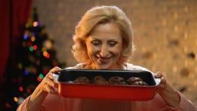 Bejaarde dame die de traditionele muffins van de Kerstmischocolade koken, wachtend familie op vooravond stock video