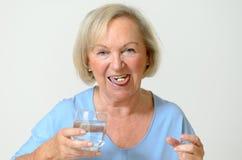 Bejaarde dame die de voorgeschreven dosis geneeskunde nemen Stock Afbeeldingen