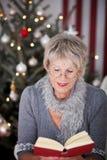 Bejaarde dame die een boek lezen bij Kerstmis Stock Foto's