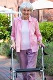 Bejaarde dame die een leurder in de tuin gebruikt stock fotografie