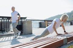 Bejaarde dame die opdrukoefeningen doen terwijl haar echtgenootjogging stock foto