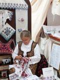 Bejaarde dame die traditioneel borduurwerk maken Stock Foto's