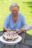 Bejaarde dame die van een plak van cake geniet Royalty-vrije Stock Foto