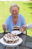 Bejaarde dame die van een plak van cake geniet Royalty-vrije Stock Foto's