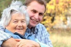 Bejaarde dame en jonge mens Royalty-vrije Stock Foto's