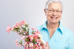 Bejaarde dame met bloemen het glimlachen Stock Foto's