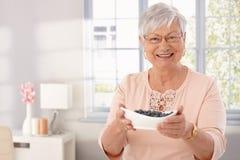 Bejaarde dame met kom van bosbes Royalty-vrije Stock Foto's