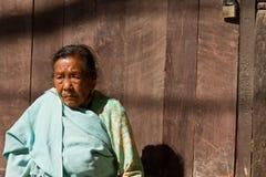 Bejaarde damezitting in de zon in Katmandu, Nepal Royalty-vrije Stock Foto