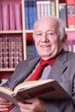 Bejaarde in de bibliotheek royalty-vrije stock afbeelding
