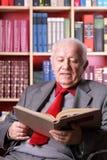 Bejaarde in de bibliotheek stock afbeelding