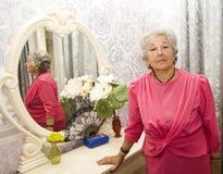 Bejaarde dichtbij spiegel Stock Foto's