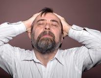 Bejaarde die aan een hoofdpijn lijden Stock Foto