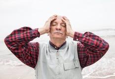 Bejaarde die aan een hoofdpijn op overzeese achtergrond lijden stock foto's