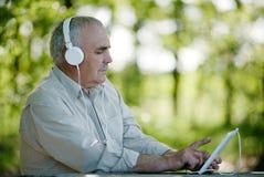 Bejaarde die aan muziek op een tablet luisteren Stock Foto's