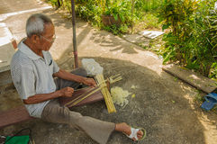 Bejaarde die bamboestroken voorbereiden om mat te maken Stock Afbeeldingen