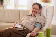 Bejaarde die bloeddruk meten Royalty-vrije Stock Foto's