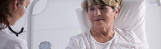 Bejaarde die dame door arts wordt onderzocht Stock Afbeeldingen