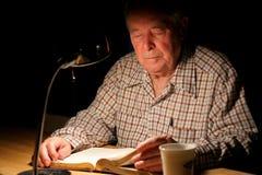Bejaarde die de Bijbel bestudeert stock foto's