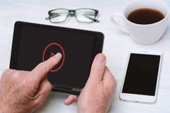 Bejaarde die digitale tablet met kop van koffie houden en glasse Royalty-vrije Stock Foto